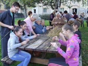 Účastníci dielní pripravujú materiál zo stebiel pšenice