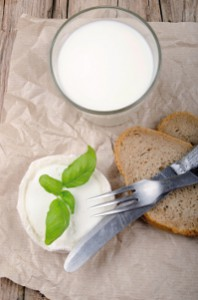 goat cheese, basil,  bread and milk on a country house kitchen table