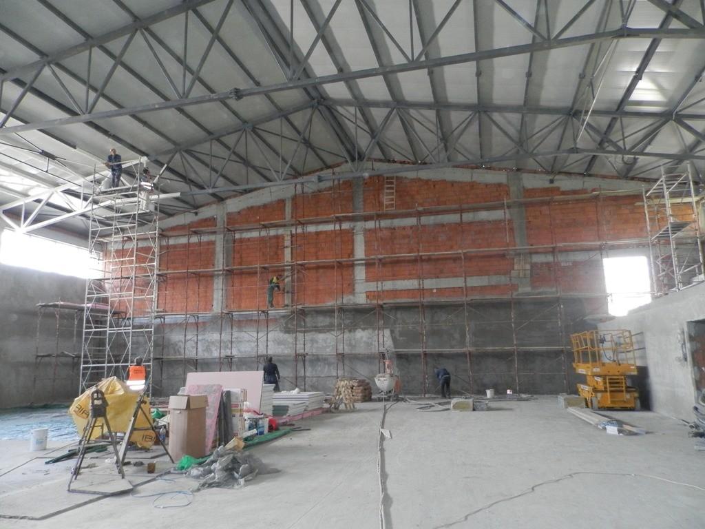 Pokým jedni majstri natierajú železnú konštrukciu krovu vo vnútri športovej haly...