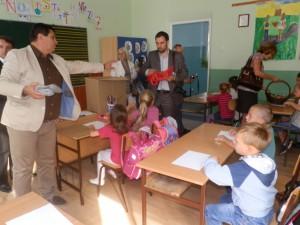 Predseda Staropazovskej obce Đorđe Radinović (zľava) udeľuje darčeky pazovským prvákom